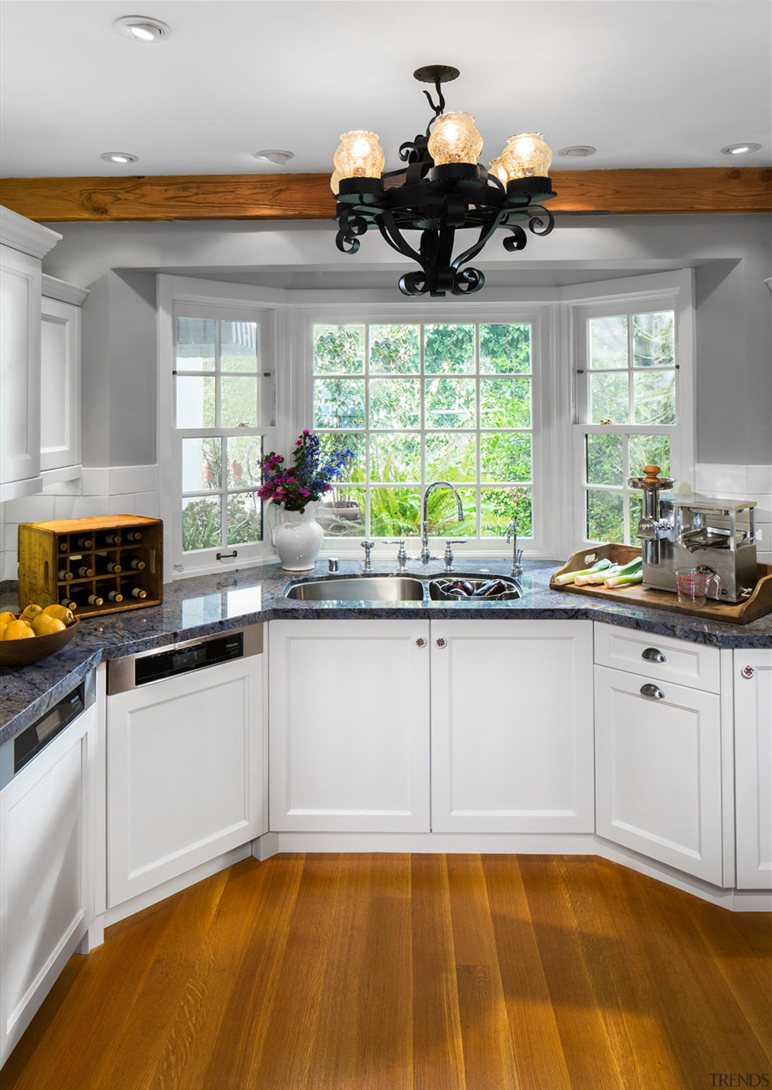 A bay window at one end of this cabinetry, countertop, cuisine ...