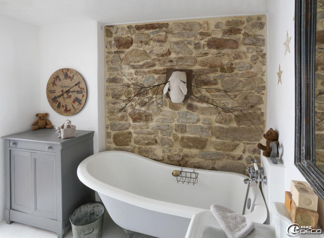 Dans une salle de bains, une vieux buffet peint en gris sert ...