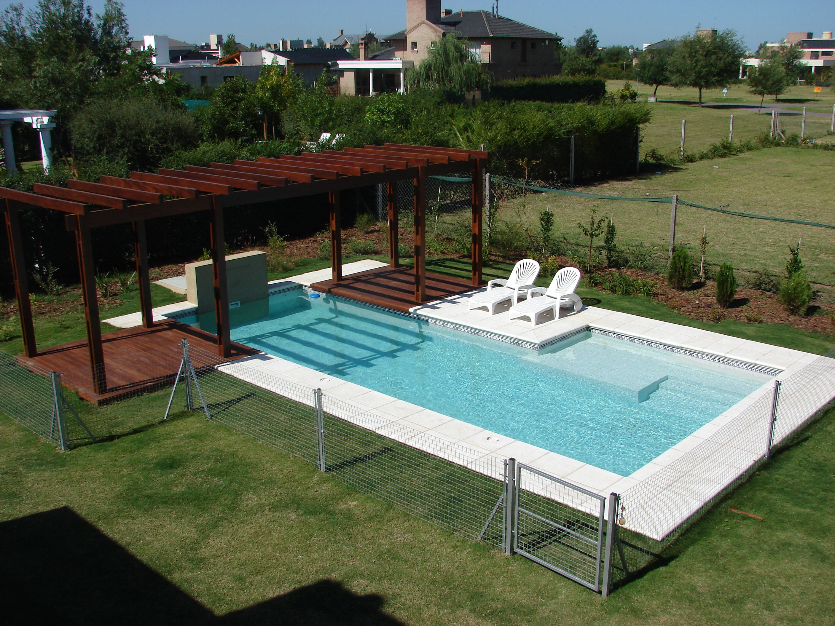 Piscina familiar pergola madera deck muro con for Piscinas de madera
