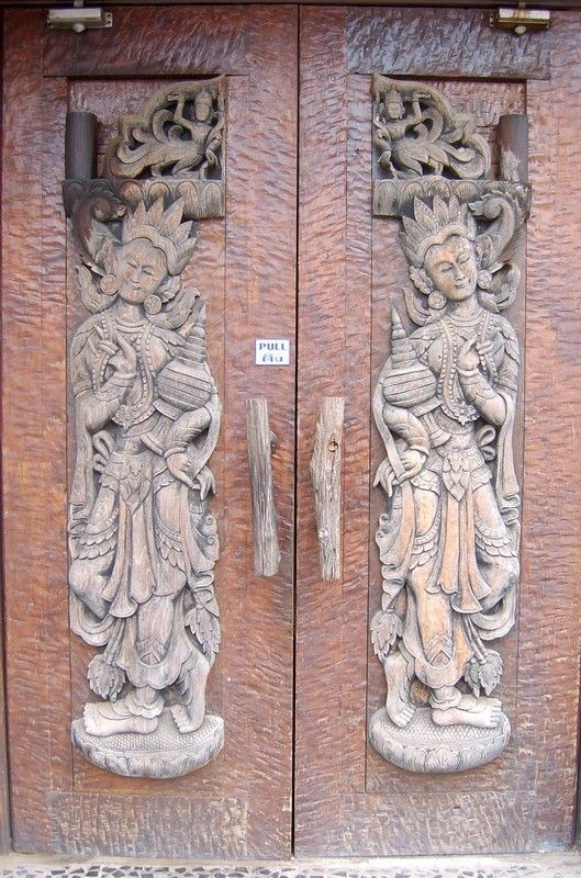 Thai teak doors with hand carved figures.