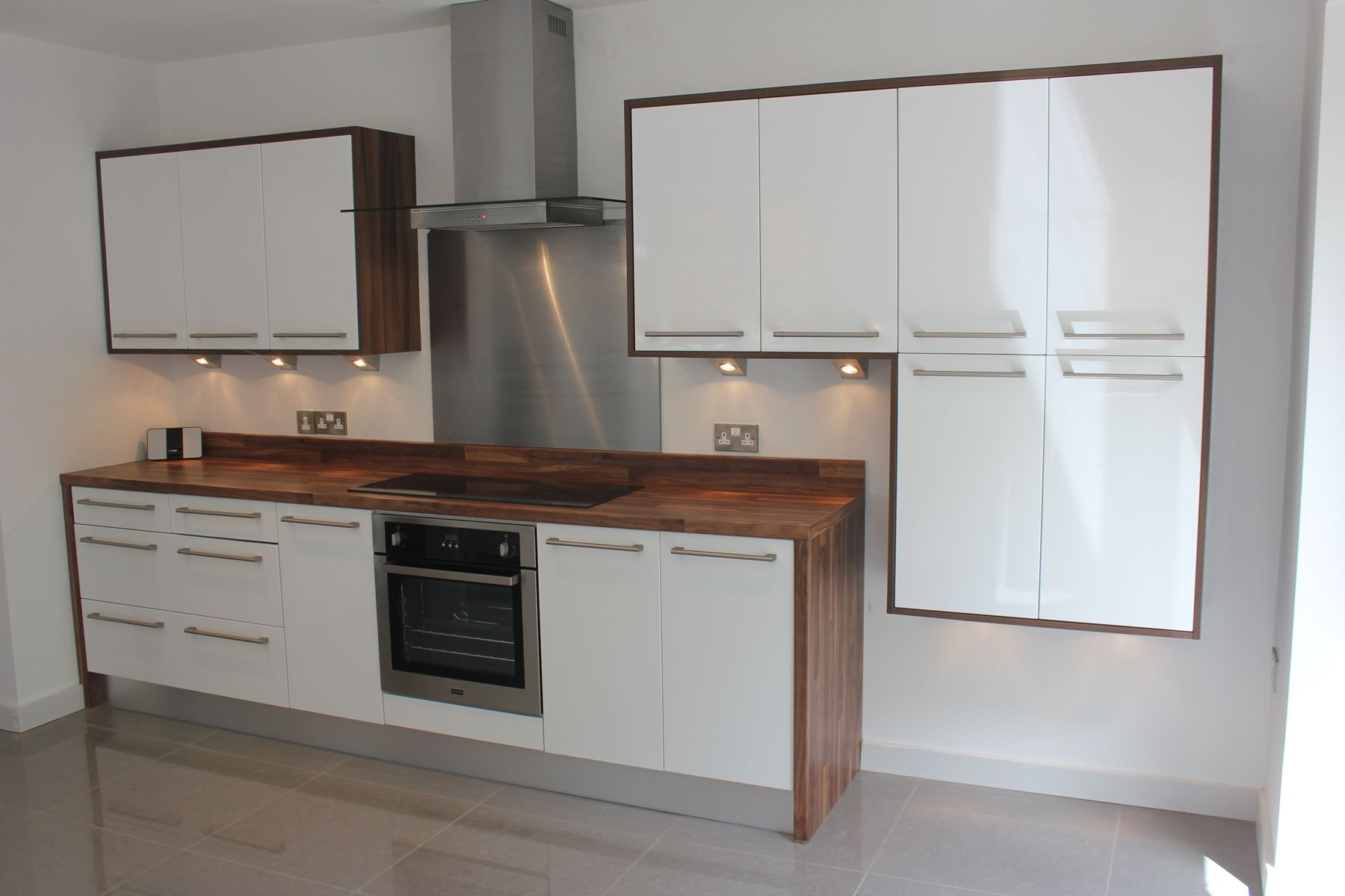white gloss kitchen with wood wrap around. Wooden