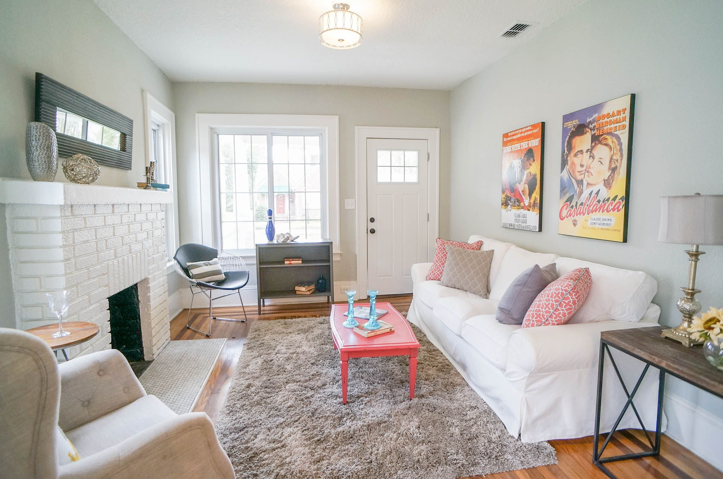 Light grey walls, wood floors, and painted white brick fireplace in ...