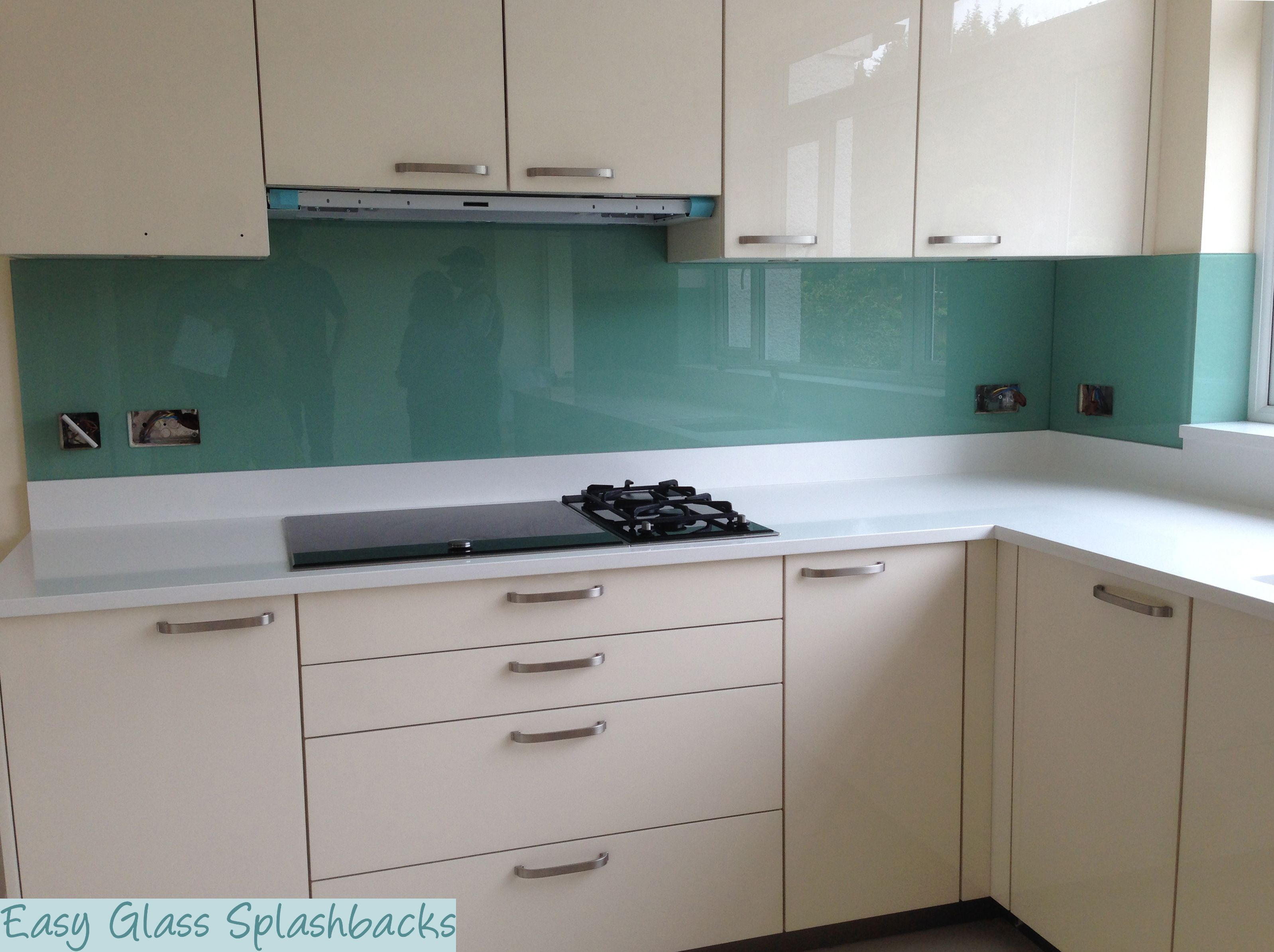 Mint green coloured glass splashback in a white kitchen for Coloured kitchen units uk