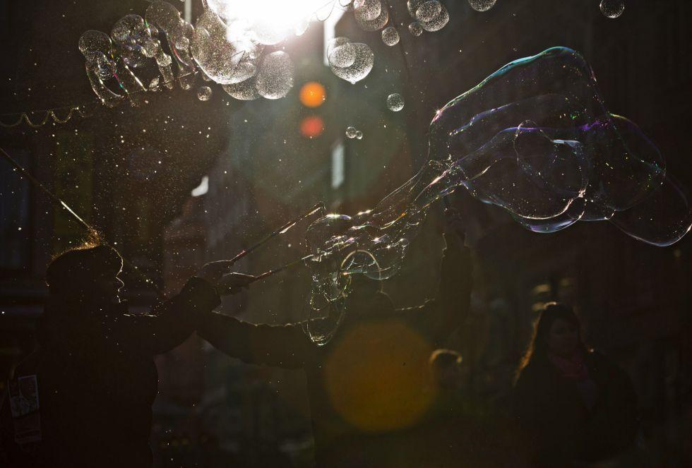 Jugando con pompas de jabón en la Plaza Wenceslao de Praga (República Checa). El intenso frío hace que las pompas se hielen al contactar con el aire