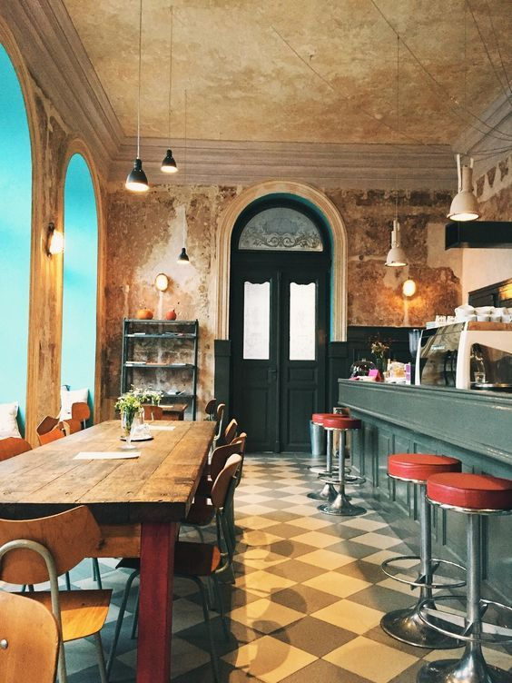 Bar with retro stools and industrial style lamps in Cafe Cafe Letka Prague.