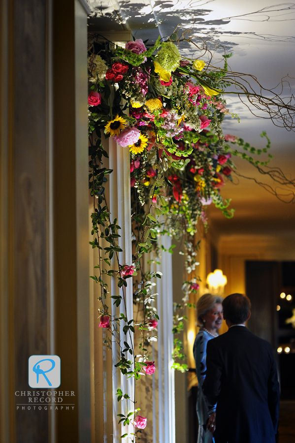 Columns Topped With Sprays Of Mixed Flowers Cascading Greenery