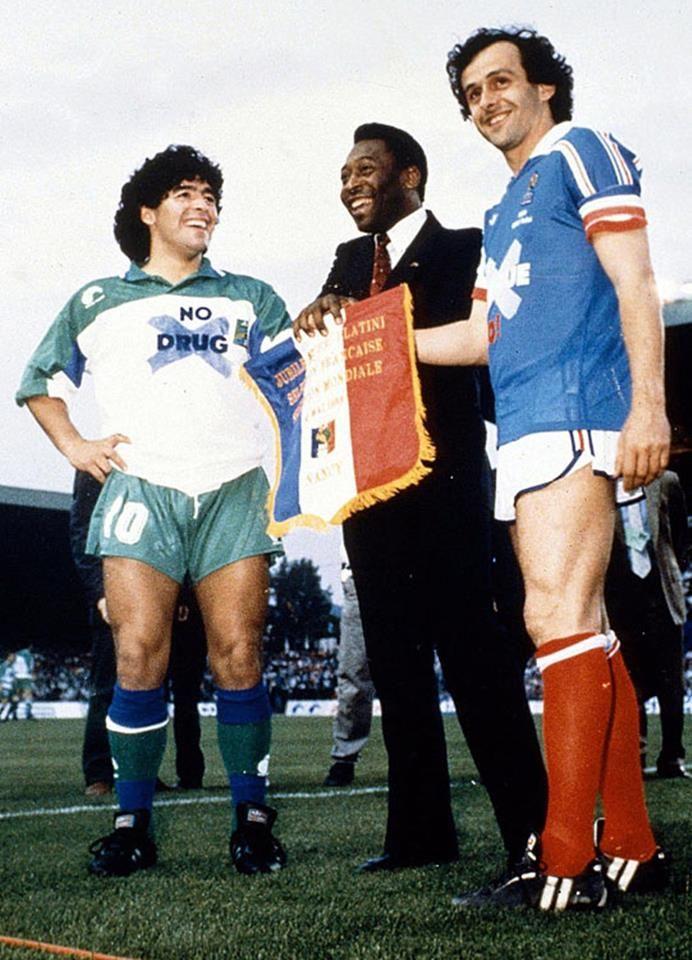 """Maradona, Pelé e Platini se encontraram durante a despedida do craque francês de sua seleção, num amistoso entre França e """"Resto do Mundo"""" disputado em 23/05/1988. O detalhe """"curioso"""" fica para o fato de Maradona estar usando uma camiseta escrito """"No Drug"""", ou seja, """"Diga Não às Drogas"""". Irônico!"""