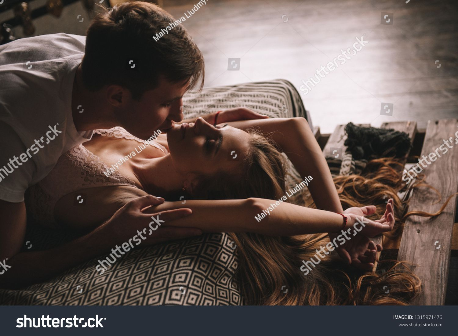 Couple On The Bed In The Bedroom Dark Interior Hugs And Kisses