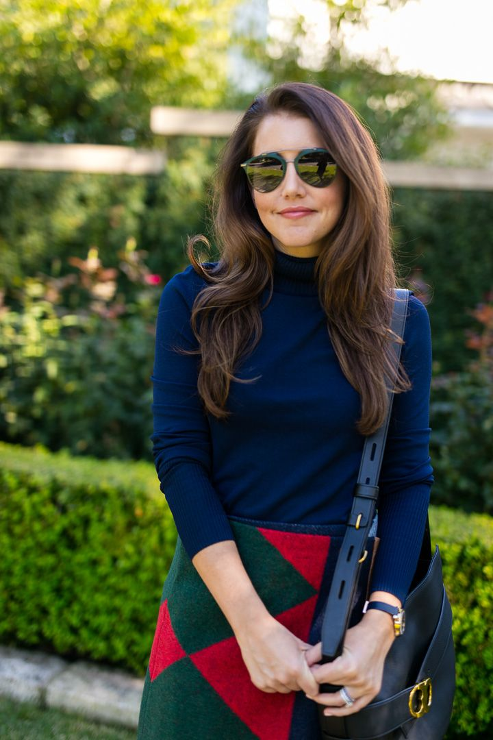 Amy Havins wears a tory burch color clocked skirt and over the knee boots.