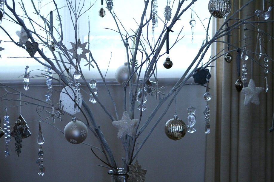 twig christmas tree with lights the branches are standing in a long spaghetti jar thats been weighed