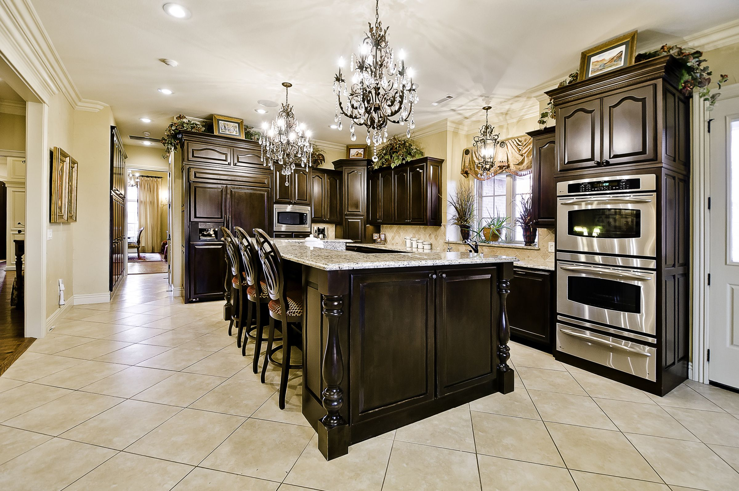 Iron And Crystal Chandeliers Over Island Kitchen Islands