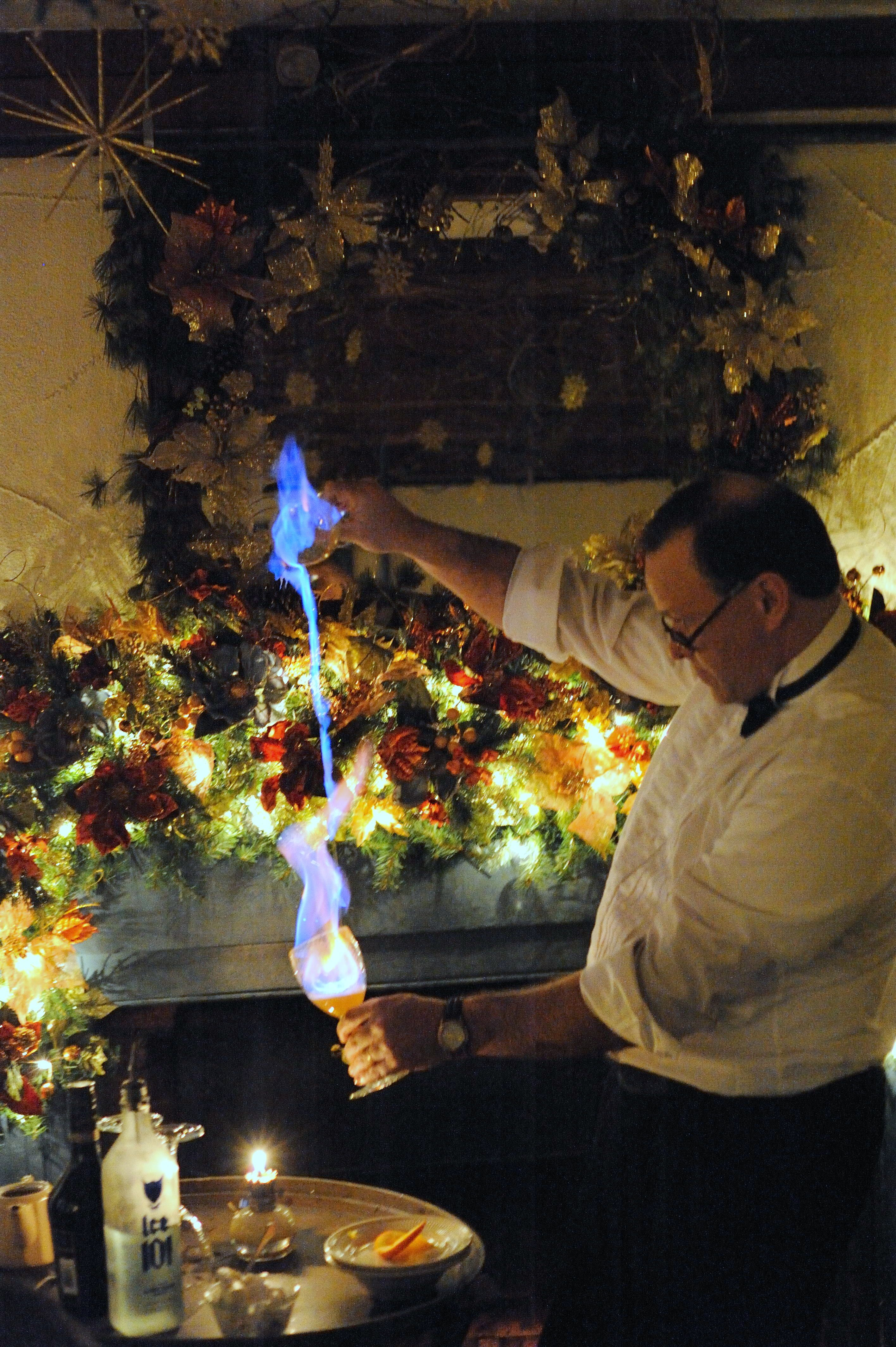 """Photo of Alan Cassell, waiter at 1785 Inn & Restaurant  http://www.the1785inn.com/ , preparing one of their signature flaming drinks, the """"Cocoa Lava."""" 1785 Inn & Restaurant is located at a Scenic Overlook in the White Mountains of NH between North Conway, NH and Jackson, NH. One of the top 15 views in the world from a hotel or inn."""