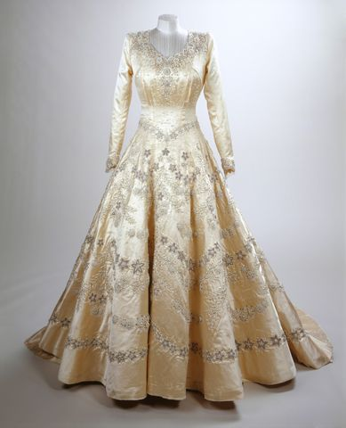 Hartnell visualized a bridal gown of fine pearl embroidery in a floral design, and cites as his inspiration Botticelli's painting of Primavera, trailed with garlands of flowers. The dress has a simple cut with fitted bodice, heart-shaped neckline, low v-pointed waist and floorlength panelled skirt. It is made from duchesse satin.