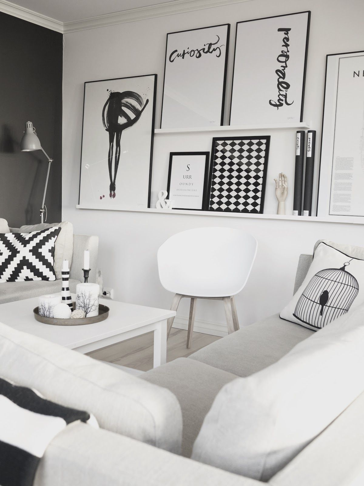 Really creative way to bring a black & white palette to life with use of pictures and pattern #LivingRoom