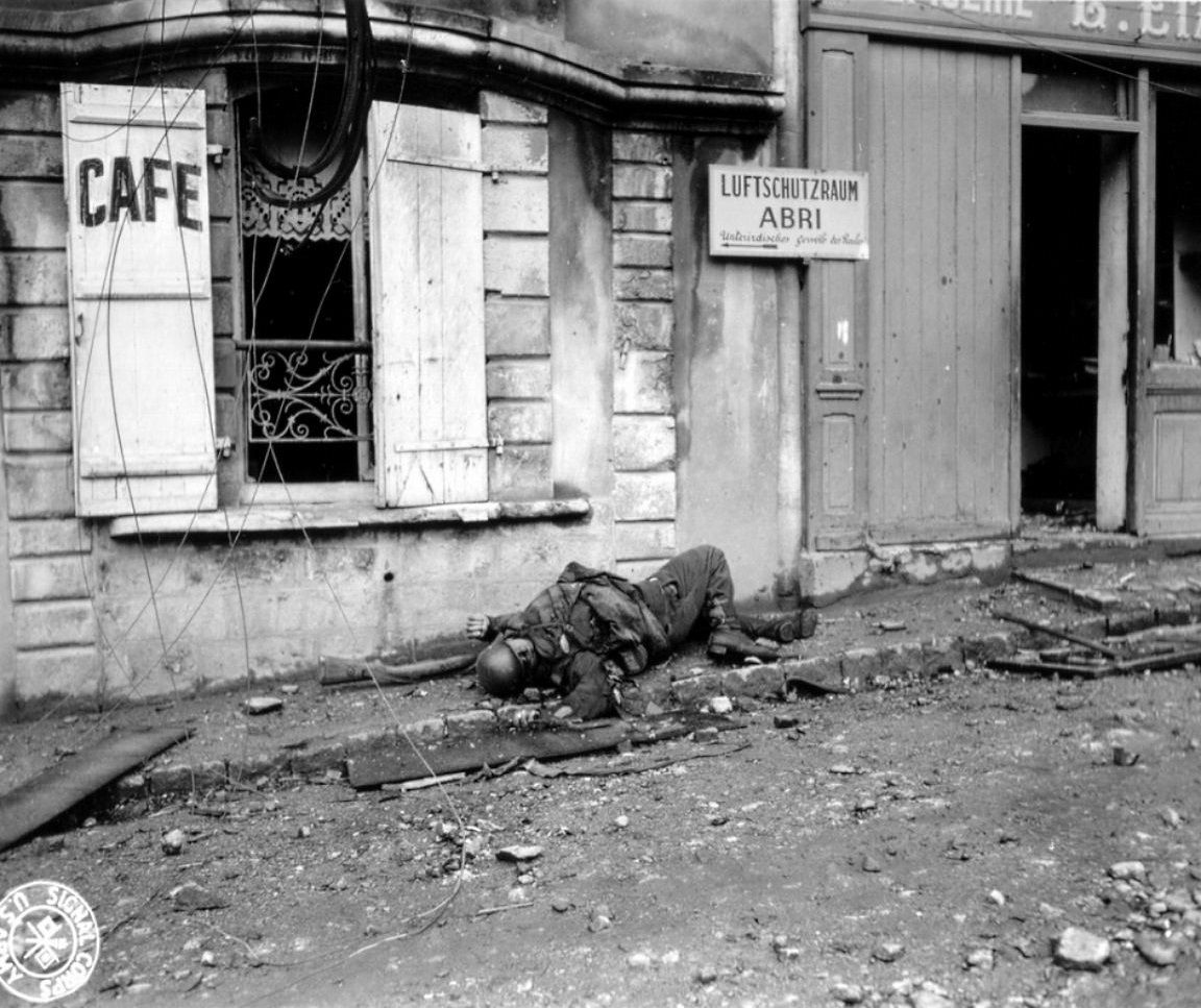The body of a German soldier lies in front of a café with a sign pointing to the direction ofthe entranceof the Roulesunderground vaults, used as air raid shelters,during the Battle of Cherbourg. The battle was part of the larger Battle of Normandy and was fought immediately after the successful Allied landings on 6 June 1944. American troops isolated and captured the fortified port, which was considered vital to the campaign in Western Europe, that ended on 30 June 1944.