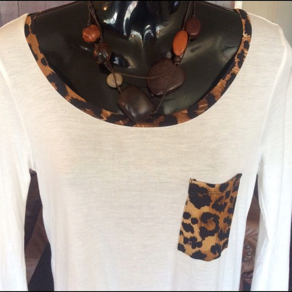 A LITTLE WILD So soft describes this Long sleeve, Ivory top. Animal print around the neck & wrist. Top left pocket is also animal print. The back has a zipper. Stretchy. Never worn . Super cute top!!  NWOT Tops