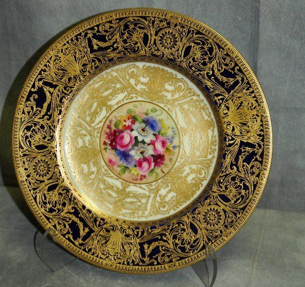 Fine Royal Worcester porcelain plate with blue ground and overall gilt decoration and floral decorated centre painted by Ernest Phillips. Signed E Phillips.