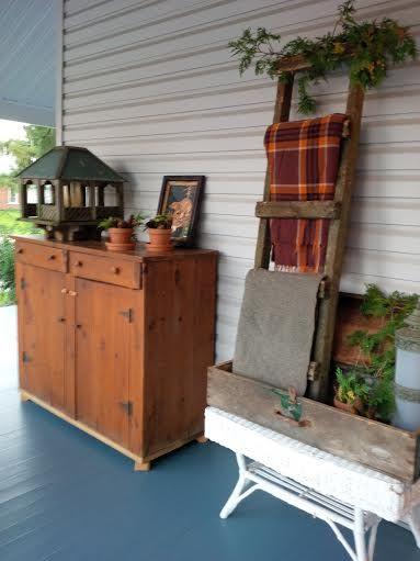 Outdoor fall decor....reclaimed ladder, woolen blankets, antique tool chest, primitive cabinet, rustic bird feeder, evergreen