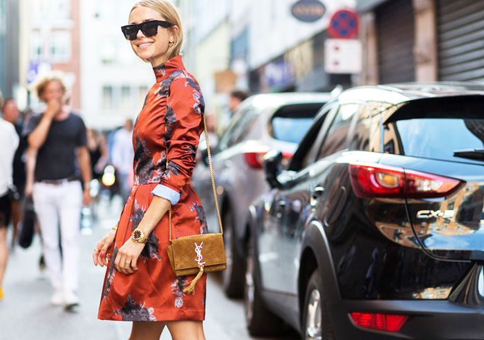 Pernille Teisbaek wears an orange floral dress with a turtleneck, suede Saint Laurent bag, and rectangular sunglasses