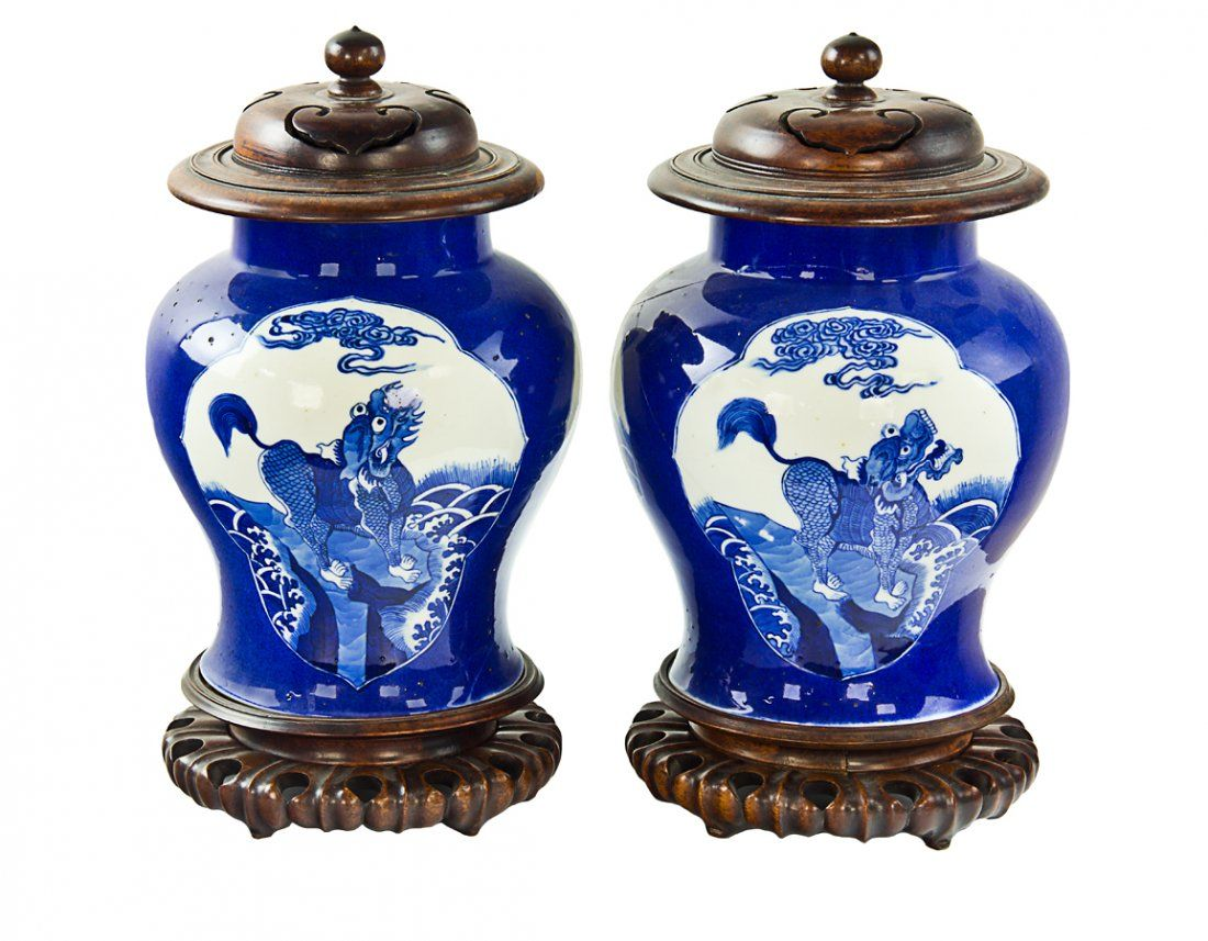 Pair of Chinese blue and white baluster vases, probably Kangxi period (1662-1722), decorated with panels of mythical beasts, each vase with wood cover and wood stand. H. 245mm