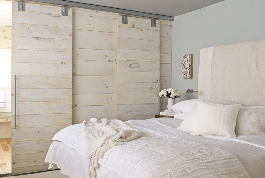 The homeowners of this Massachusetts cabin freed up floor space in their small guest bedroom by installing sliding barn doors.   - CountryLiving.com