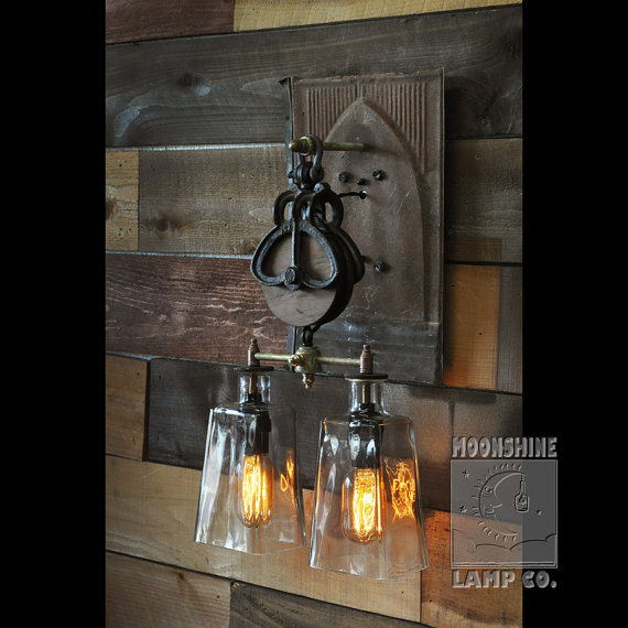 A custom wall sconce made from two recycled 1800 tequila bottles a pulley and vintage