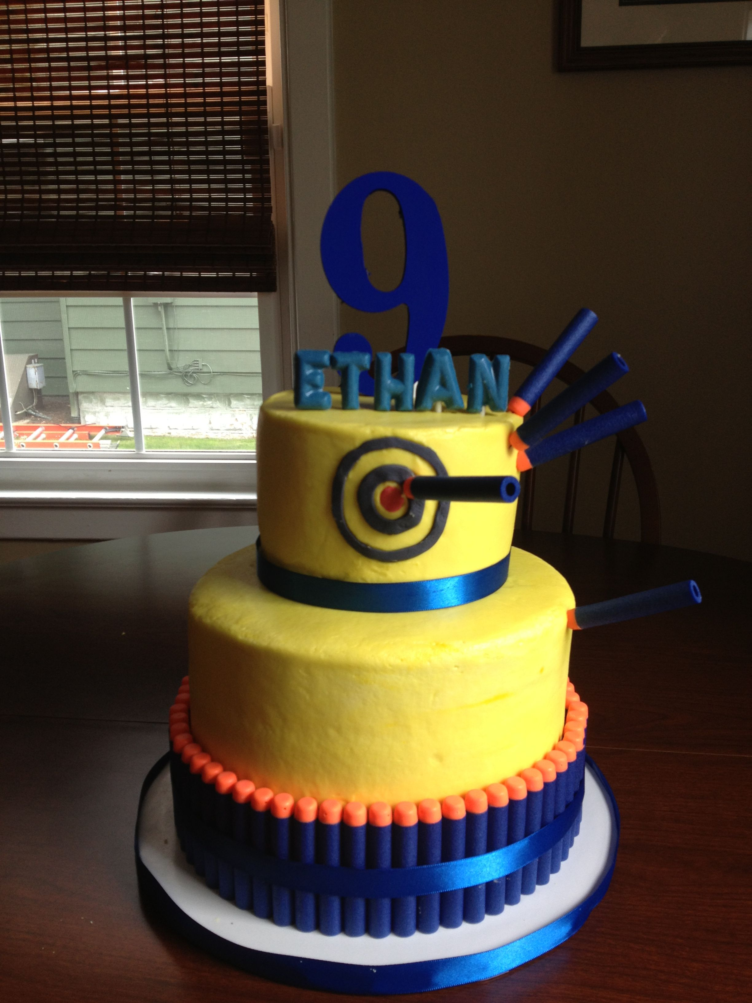 nerf birthday cake 9 triple layer cake w 6 topper wooden 9 and chocolate name letters nerf darts placed around base cake secured with blue ribbon