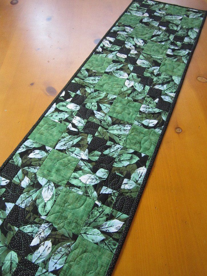 The leaves in this table runner will look stunning on your table. The black background enhances the colors. There is mostly green for the leaves with a touch of blue. There is silver metallic in the b