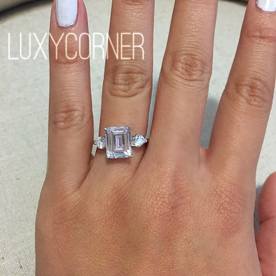 Stunning 3 Carat Emerald Cut Rectangle Simulated Diamond Flanked By Faint Heart Shaped Lab Diamonds On Each Side Solid Sterling Silver Plated With