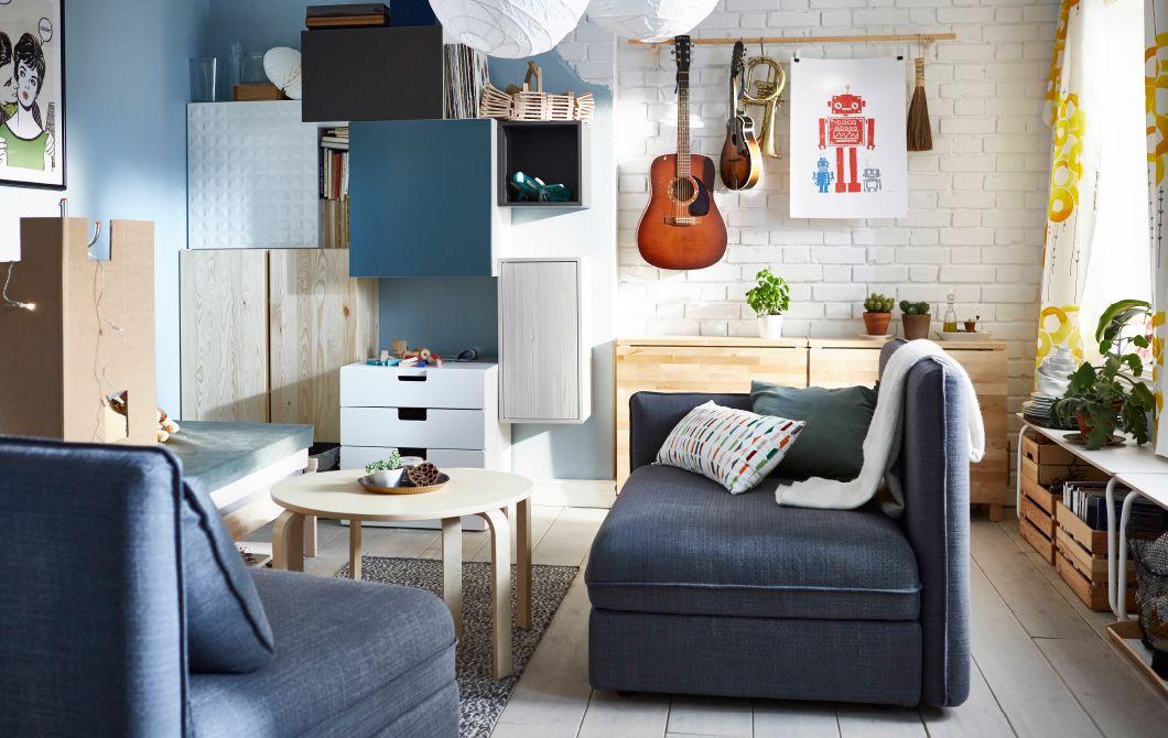 Ein Wohnzimmer mit Sitzelementen, einer Wand mit unterschiedlichen