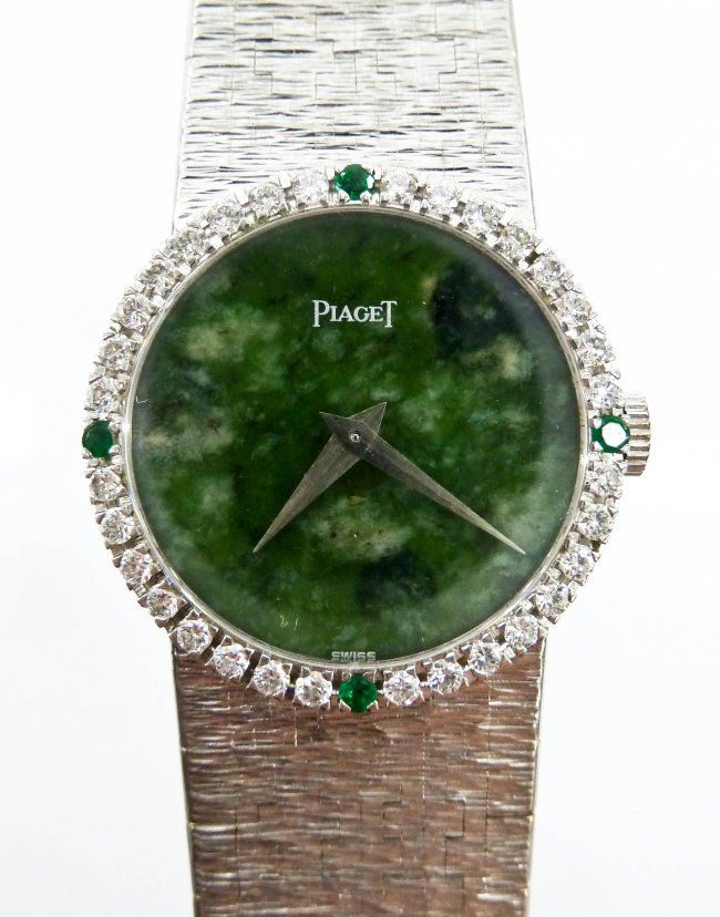 Lot 226- Lady's Piaget 18k White Gold Wristwatch. It has a diamond and emerald 24mm bezel with jade face. Solid 18k white gold bracelet band marked ''PIAGET 750'' on clasp. Back of case is marked ''9706 A 6 177237''. Movement in working order. It weighs 52.3 grams total. Search terms: women's wrist watch, art deco style, chinese, china.