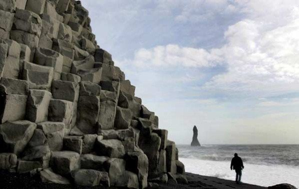 Unusual Beach Rock Formations | An unusual rock formation towers over a man walking on the black ...