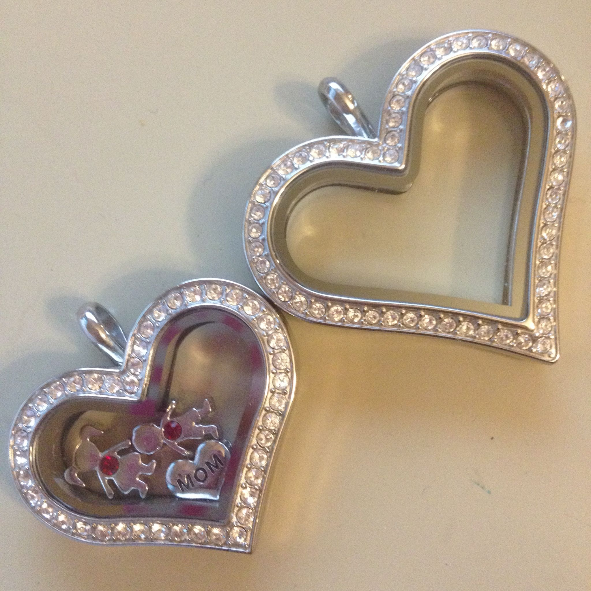 The 2 heart lockets from origami owl for size comparison - and to give an idea on how many kids fit inside. Kids with birthstone charms are no longer available. Kids charms no longer have birthstones in them.