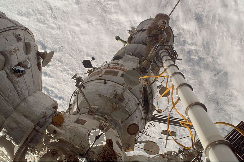 Flight Engineer Kononenko photographs commander Volkov operating the manual Strela crane holding him. The commander stands on Pirs and has his back to the Soyuz spacecraft. Zarya is seen to the left and Zvezda across the bottom of the image.