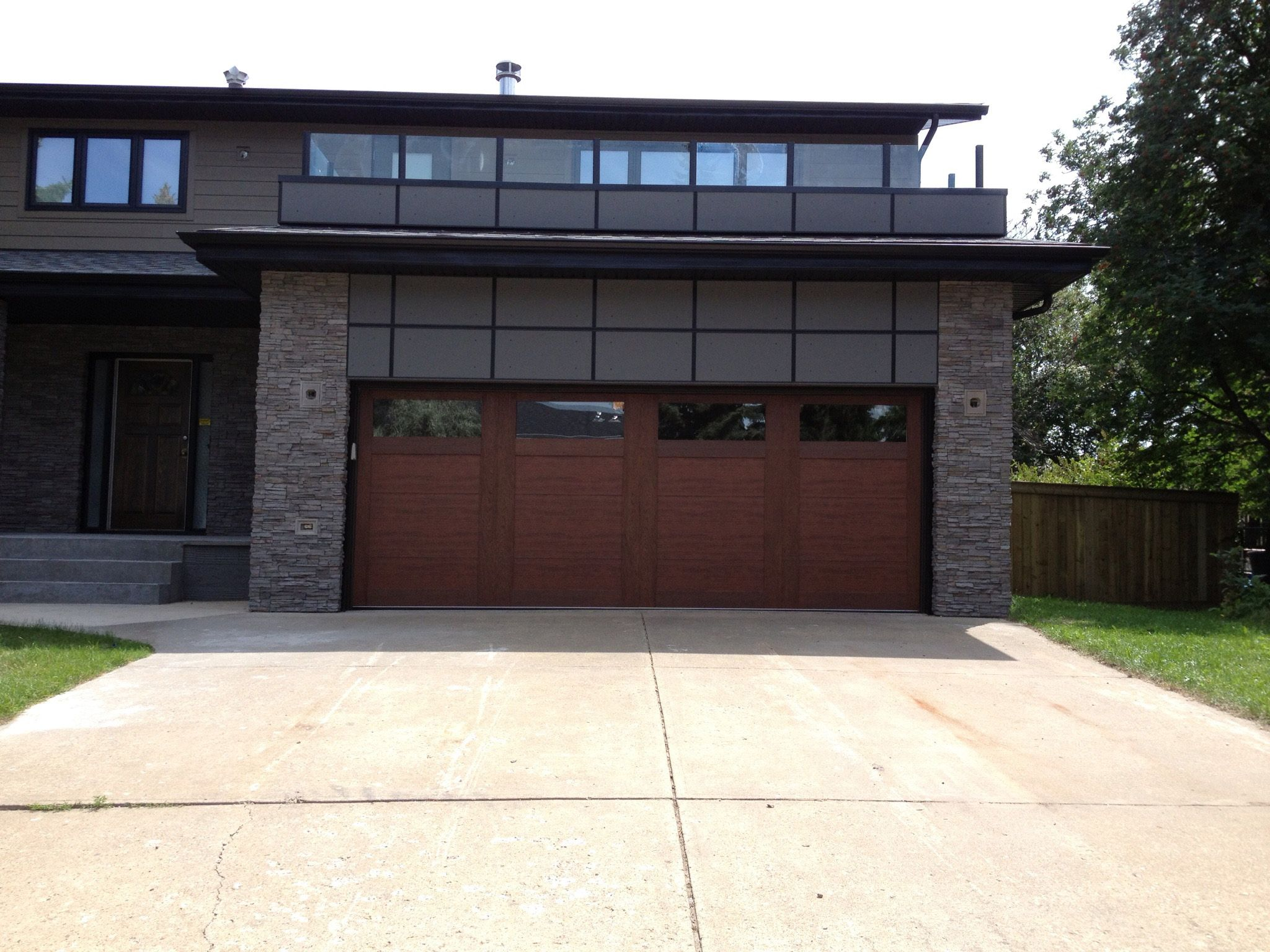 A stained steel garage door adds warmth to this for Garage door with entry door