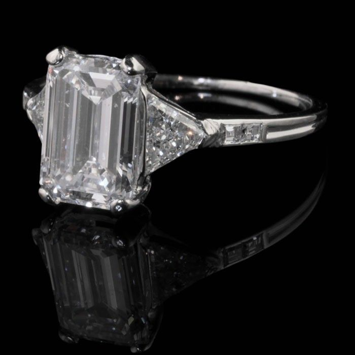 TIFFANY & Co. New York.Art Deco c1925.Platinum and diamond ring with a central emerald-cut diamond flanked either side by triangular and square-cut diamonds