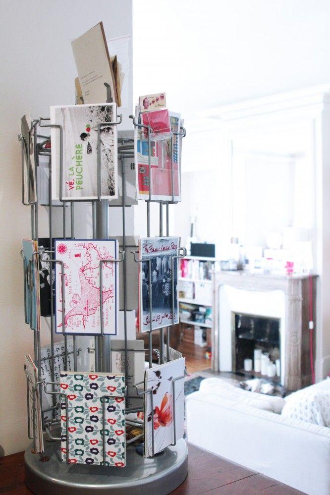 A gauche : Dans l'entrée, elle a rangé des cartes postales graphiques, comme celle de Lolita Picco, dans un tourniquet  AMPM.