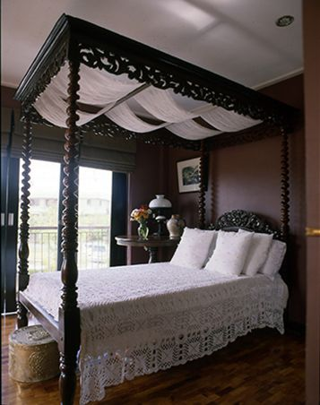 The four poster bed, an heirloom, is from the 1920s, giving the room an elegant colonial Filipino feel. The white lace throw pillows complement the dark wood.