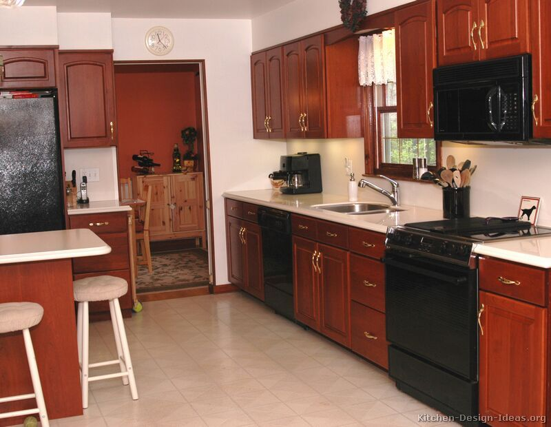 Traditional medium wood cherry kitchen cabinets with black for Brown kitchen cabinets with black appliances