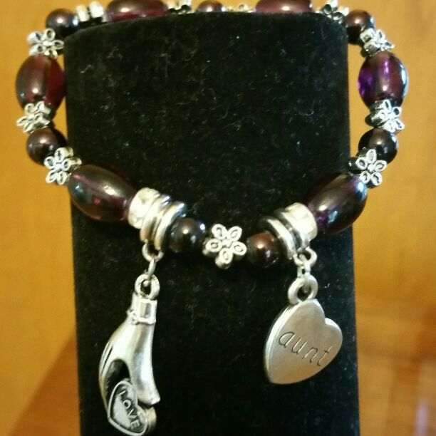 "Great gift idea for that special Aunt.  This is a beautiful stretch bracelet made with deep rich purple glass beads and silver alloy flower spacers.   It has dangle charms..a hand holding a heart that says love and a heart that says AUNT. Fits up to 7""wrist"