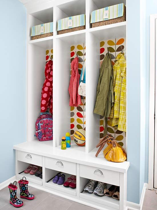 Modern leaf-patterned wallpaper lines the back of this handy locker unit. It also adds a dash of color to this functional mudroom.