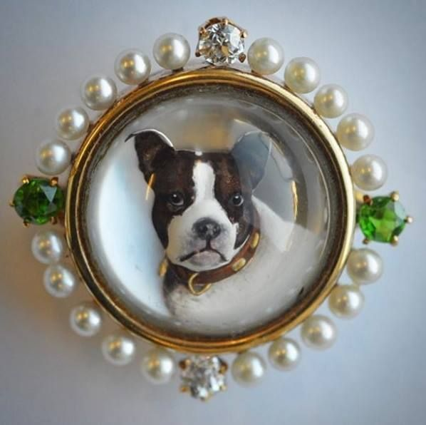 An important circular Essex crystal brooch in the form of a dog with diamond and green garnet frame in gold mount.