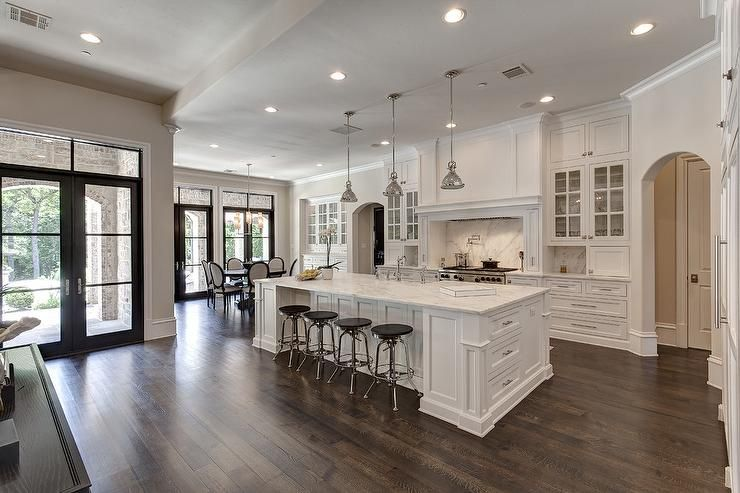 Stunning kitchen features three industrial pendants illuminating a white center island topped with white marble fitted with a sink lined with Restoration Hardware Vintage Toledo Stools.