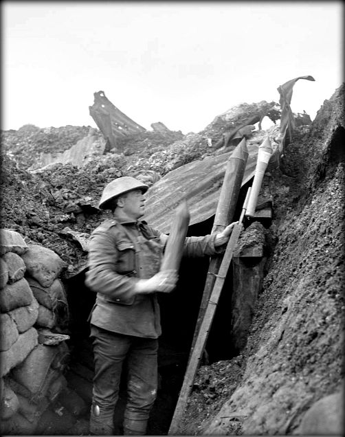 WWI, 6 Feb 1918; A man of the 6th York and Lancaster Reg. fixing rockets in a front line trench, near Cambrin. ©IWM Q 8457
