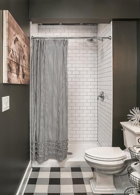White subway tiles frame a wall in a walk-in shower with a black and ...