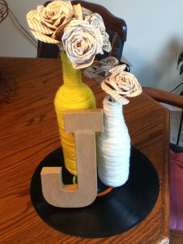 My wedding centerpiece! Two to three vases per table (with varying amounts of book page flowers) and some kind of neutral-colored J, all sitting on a record!