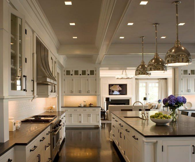 expansive kitchen flowing into the family room beyond creamy shaker style cabinets with iron pulls