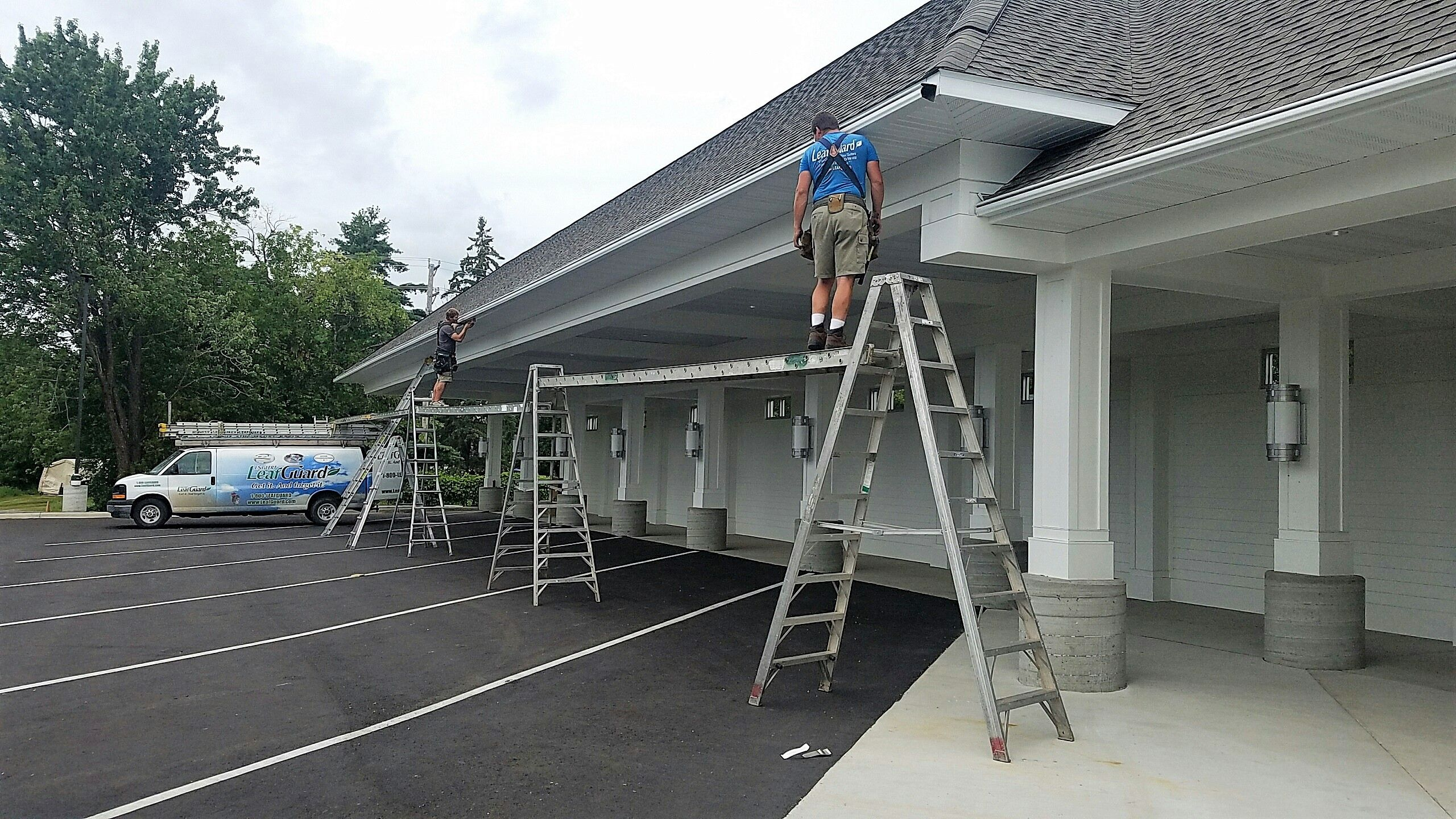 Here Our Lead Installers Jason And Travis Are Installing A Run Of Leafguard Gutters On The Executive Express Building I Seamless Gutters Gutters Installation