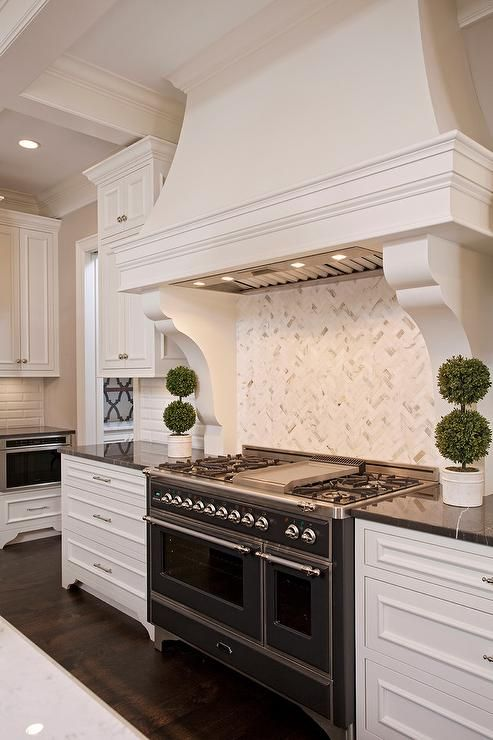 In This Large White Kitchen A Grand French Hood Makes A