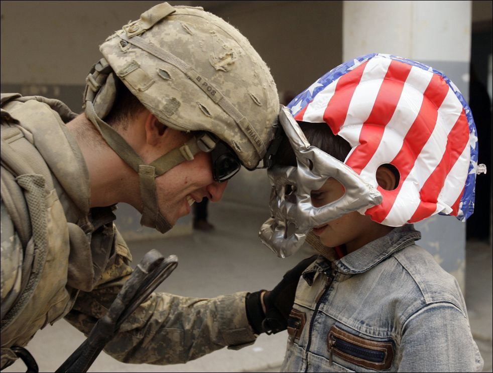 American soldier in worn uniform, and Iraqi boy in toy